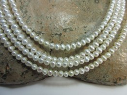 Perlen klein, Saatperlen potatoeform auf Stahllitze gefädelt
